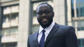 Homem de negócios afro-americano bem sucedido que olha as mãos de cruzamento da câmera, comércio video estoque