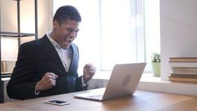 Homem de negócios afro-americano Celebrating Success ao trabalhar no portátil Imagens de Stock