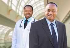 Homem de negócios afro-americano e doutor Inside Medical Building imagem de stock