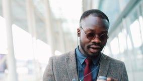 Homem de negócios afro-americano feliz que escuta a música nos fones de ouvido no smartphone, andando fora do escritório e engraç filme