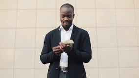 Homem de negócios afro-americano feliz que guarda uma quantidade de dinheiro grande em suas mãos Está na rua perto do escritório vídeos de arquivo