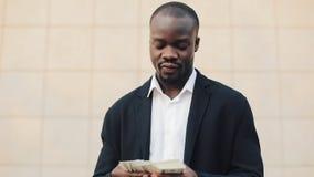 Homem de negócios afro-americano feliz que guarda uma quantidade de dinheiro grande em suas mãos Está na rua perto do escritório filme