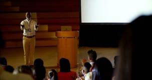 Homem de negócios afro-americano maduro que fala no seminário do negócio no auditório 4k video estoque