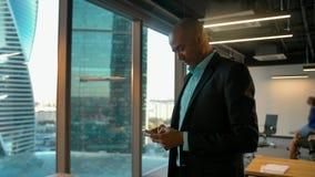 Homem de negócios afro-americano na roupa formal que conversa no mensageiro com smartphone filme