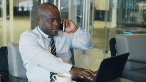 Homem de negócios afro-americano na roupa formal que fala em seus smartphone e rede da consultação ao olhar seu portátil dentro video estoque