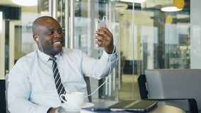 Homem de negócios afro-americano na roupa formal que sorri e que fala a sua família através da câmara web do smartphone em um mod video estoque