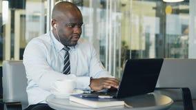 Homem de negócios afro-americano no vestuário formal que trabalha e que surfa meios sociais no portátil ao escutar a música com video estoque