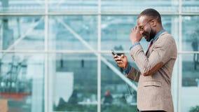 Homem de negócios afro-americano nos óculos de sol que fala no telefone com os fones de ouvido perto do prédio de escritórios Neg vídeos de arquivo