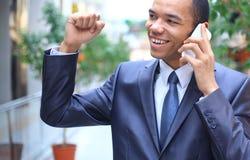 Homem de negócios afro-americano novo no telemóvel fotografia de stock royalty free