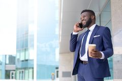 Homem de negócios afro-americano novo que fala a um cliente no telefone com um copo do coffe durante o tempo da ruptura Copie o e fotos de stock