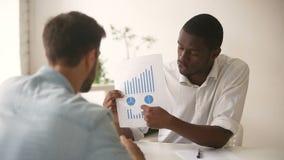 Homem de negócios afro-americano que consulta dando a apresentação ao acionista caucasiano do cliente video estoque