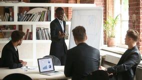 Homem de negócios afro-americano que dá a apresentação aos sócios masculinos caucasianos com flipchart filme