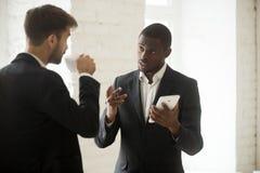Homem de negócios afro-americano que discute o app novo com o p caucasiano imagens de stock royalty free
