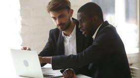 Homem de negócios afro-americano que mostra a apresentação do computador do PC ao cliente caucasiano filme