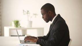 Homem de negócios afro-americano que trabalha no computador que senta-se na mesa de escritório video estoque