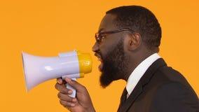 Homem de negócios afro-americano que usa o megafone à informação da propagação, notícia de comércio vídeos de arquivo