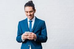 Homem de negócios afro-americano que usa o smartphone no branco imagem de stock royalty free