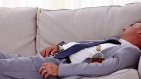 Homem de negócios alcoólico que encontra-se e que dorme no sofá video estoque