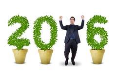 Homem de negócios alegre com números dados forma árvores 2016 Imagens de Stock Royalty Free