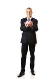 Homem de negócios alegre do comprimento completo que guarda o piggybank Fotografia de Stock Royalty Free