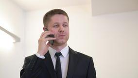 Homem de negócios alegre do retrato que sorri e que fala pelo telefone celular no escritório filme