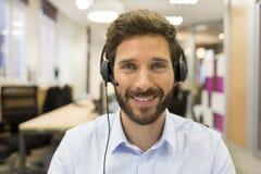 Homem de negócios alegre no escritório na videoconferência, auriculares, Fotografia de Stock