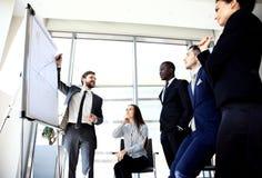 Homem de negócios alegre que discute o projeto novo do negócio com os membros de sua equipe Imagens de Stock