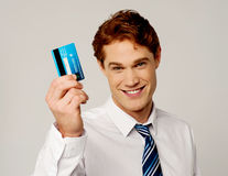 Homem de negócios alegre que guarda o cartão de crédito imagens de stock royalty free