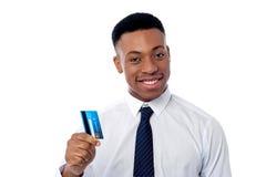 Homem de negócios alegre que guarda o cartão de crédito fotografia de stock royalty free