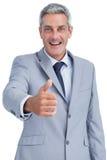 Homem de negócios alegre que olha a câmera que alcança para o aperto de mão imagem de stock
