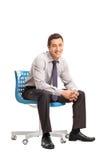 Homem de negócios alegre que senta-se em uma cadeira azul Fotografia de Stock Royalty Free