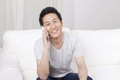 Homem de negócios alegre que usa um telefone celular no sofá Fotografia de Stock