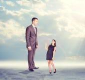 Homem de negócios alto que olha para baixo na mulher pequena dentro Fotos de Stock