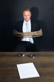 Homem de negócios amarrado com a corda que senta-se na frente da tabela imagem de stock