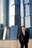 Homem de negócios amigável que está de encontro ao arranha-céus Fotografia de Stock Royalty Free