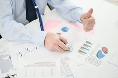Homem de negócios antes dos gráficos financeiros, polegar acima Imagens de Stock