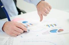 Homem de negócios antes dos gráficos financeiros, polegar para baixo Imagens de Stock Royalty Free