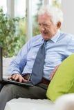 Homem de negócios aposentado que trabalha em casa imagens de stock