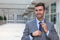 Homem de negócios arrogante que ajusta seu laço com espaço da cópia fotografia de stock