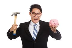 Homem de negócios asiático com martelo e mealheiro Imagens de Stock Royalty Free