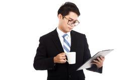 Homem de negócios asiático com uma xícara de café e uma prancheta Imagem de Stock Royalty Free