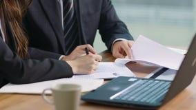 Homem de negócios asiático e mulher de negócios que discutem uma proposta no escritório