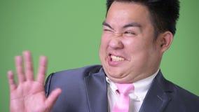 Homem de negócios asiático excesso de peso considerável novo contra o fundo verde filme