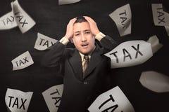 Homem de negócios asiático forçado com texto do imposto no papel foto de stock
