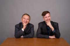Homem de negócios asiático maduro e pensamento caucasiano novo do homem de negócios foto de stock royalty free