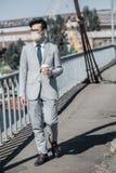 homem de negócios asiático na máscara protetora que anda na ponte com café para ir olhar o ar ausente fotos de stock