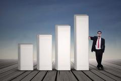 Homem de negócios asiático no terno preto que está ao lado da carta de barra Imagem de Stock