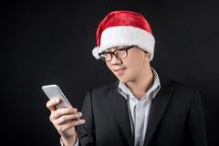 Homem de negócios asiático novo com chapéu de Santa usando o smartphone Fotografia de Stock