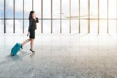 Homem de negócios asiático novo com telefone celular e a mala de viagem azul que anda no salão do aeroporto fotografia de stock