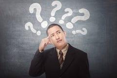 Homem de negócios asiático novo confundido com os pontos de interrogação acima de seu h fotografia de stock royalty free
